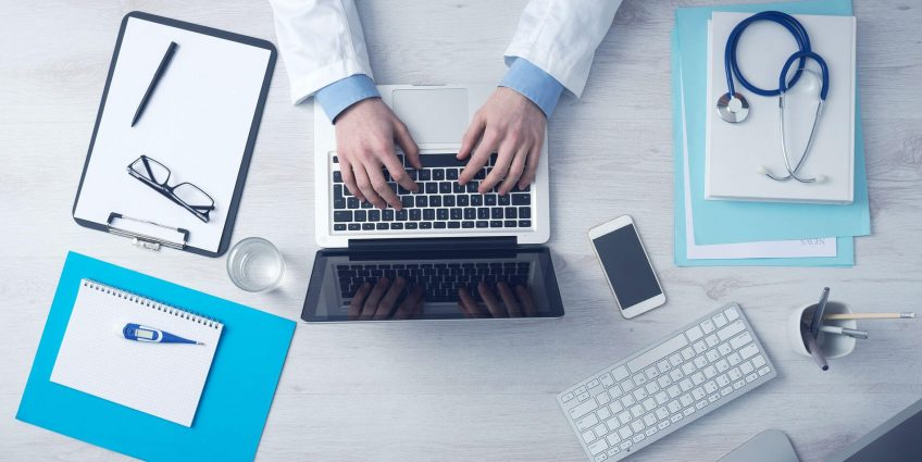 A doctor typing on the laptop