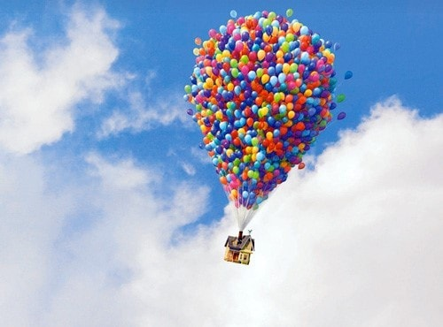 A house flying with the help of a cluster of multicolored balloons attached to it