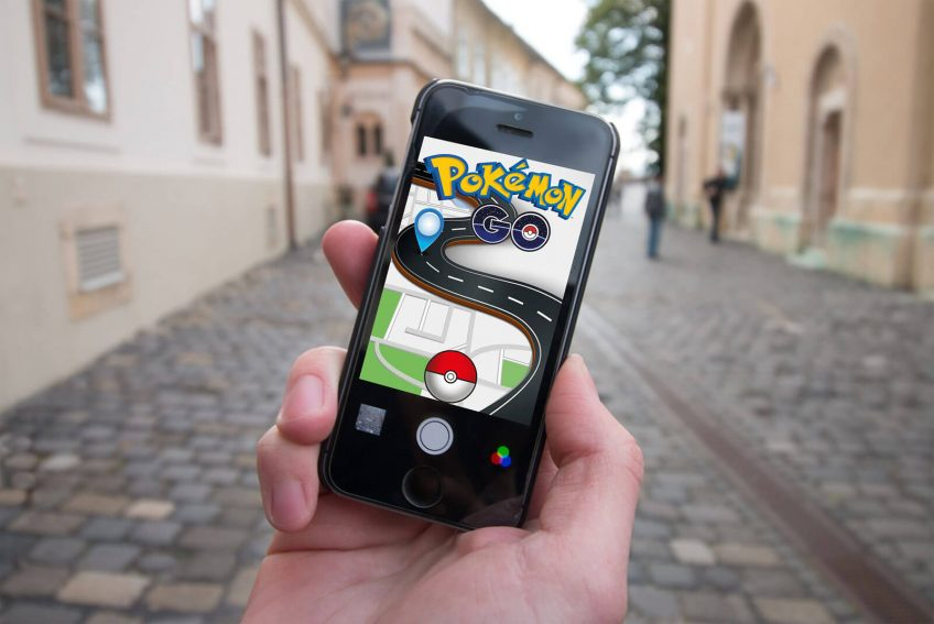 A hand holding a smartphone with a screenshot of Pokemon Go game