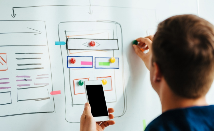 A designer making an app plan on a whiteboard